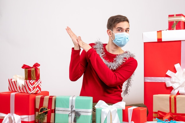 Vorderansicht junger mann mit medizinischer maske, die um weihnachtsgeschenke weihnachtsfoto sitzt