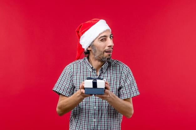 Vorderansicht junger mann mit neujahrsgeschenk auf rotem hintergrund