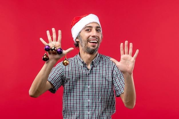 Vorderansicht junger mann mit niedlichen plastikspielzeugen auf dem roten hintergrund