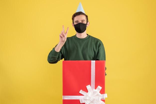 Vorderansicht junger mann mit partei-kappe, die siegeszeichen macht, das hinter großer geschenkbox auf gelbem hintergrund steht