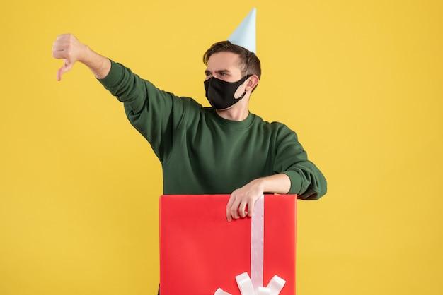 Vorderansicht junger mann mit partykappe, die daumen nach unten zeichen macht, das hinter großer geschenkbox auf gelbem hintergrund steht