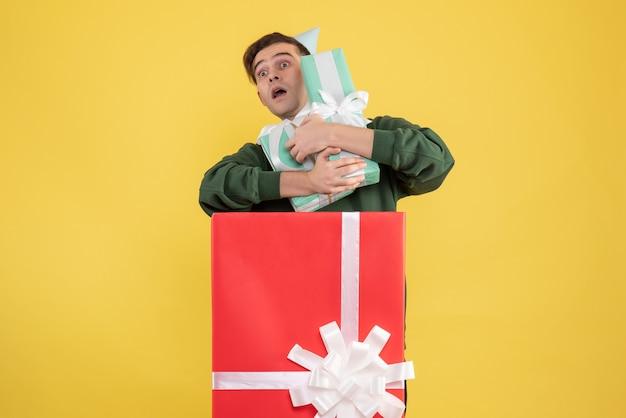 Vorderansicht junger mann mit partykappe, die geschenke hält, die hinter großer geschenkbox auf gelbem hintergrund stehen