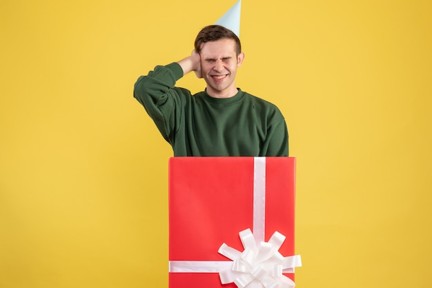 Vorderansicht junger mann mit partykappe, die seine ohren hält, die hinter großer geschenkbox auf gelbem hintergrund stehen