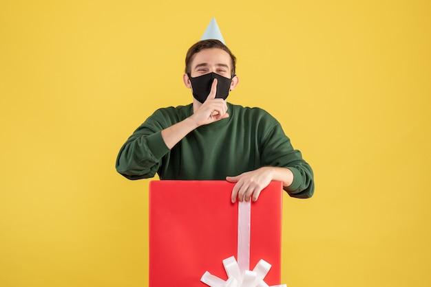 Vorderansicht junger mann mit partykappe, die shh zeichen macht, das hinter großer geschenkbox auf gelbem hintergrund steht
