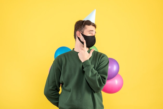 Vorderansicht junger mann mit partykappe und bunten luftballons, die auf freiem platz des gelben hintergrunds stehen
