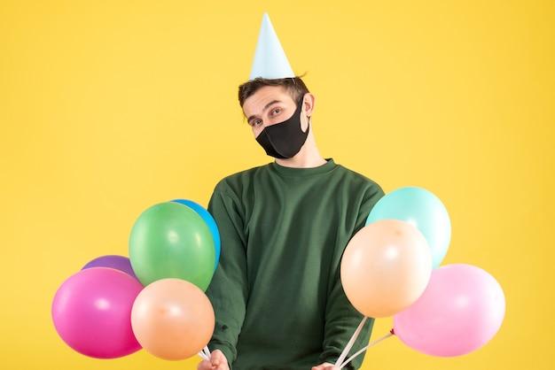Vorderansicht junger mann mit partykappe und bunten luftballons, die auf gelbem hintergrundkopierraum stehen
