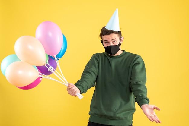 Vorderansicht junger mann mit partykappe und bunten luftballons, die hände auf gelb öffnen