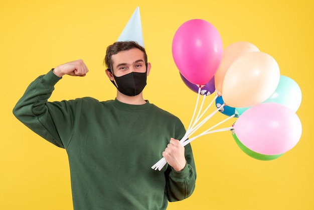 Vorderansicht junger mann mit partykappe und bunten luftballons, die muskel stehen auf gelb zeigen