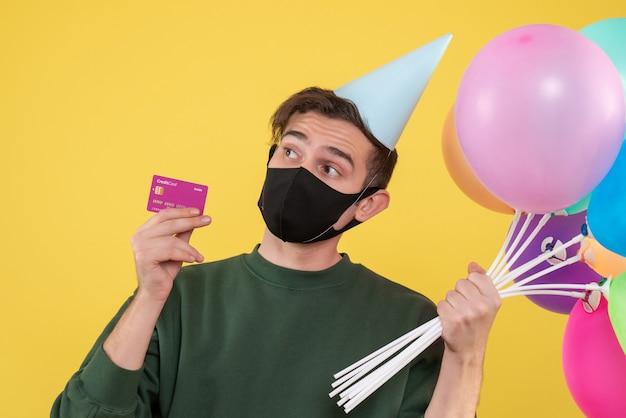 Vorderansicht junger mann mit partykappe und schwarzer maske, die karte und luftballons auf gelb hält