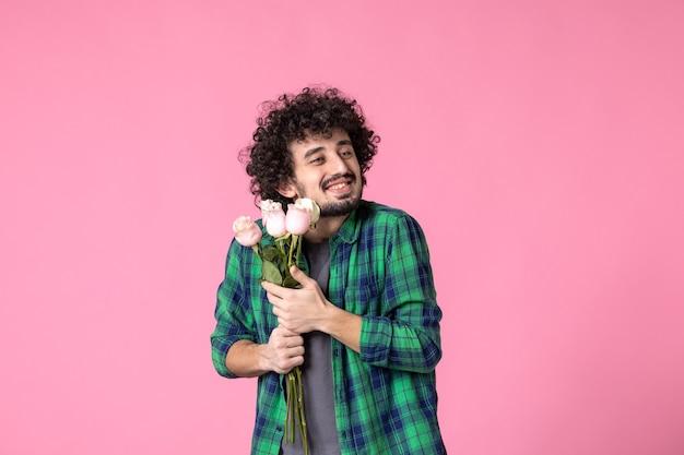 Vorderansicht junger mann mit rosa rosen als geschenk zum frauentag auf rosa farbe