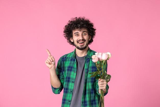 Vorderansicht junger mann mit rosa rosen auf rosa farbe