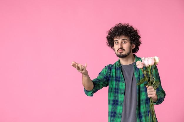 Vorderansicht junger mann mit rosa rosen auf rosa