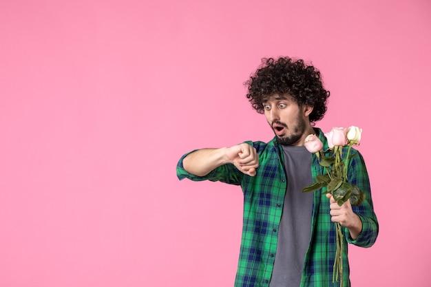 Vorderansicht junger mann mit rosa rosen, die zeit auf rosa überprüfen