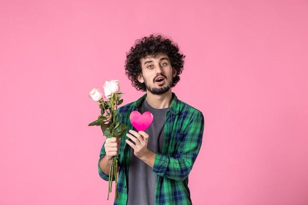 Vorderansicht junger mann mit rosa rosen und herzaufkleber auf rosa