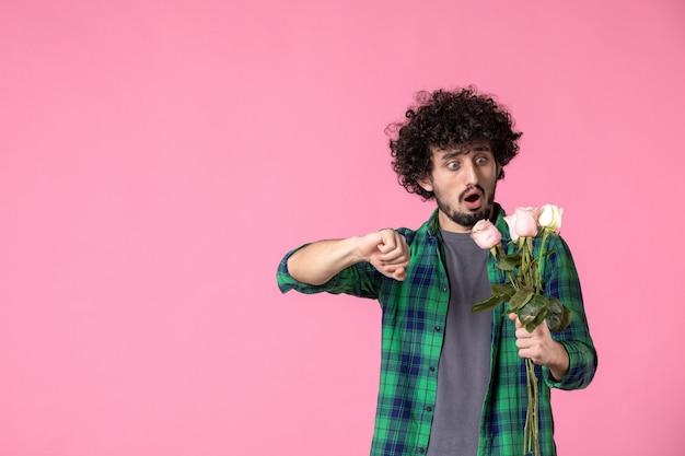 Vorderansicht junger mann mit rosa rosen zu spät zu einem rosa date