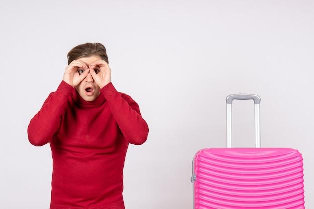 Vorderansicht junger mann mit rosa tasche auf weißem hintergrund