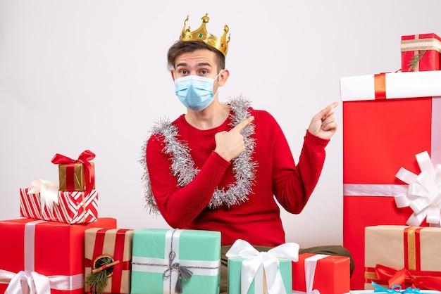 Vorderansicht junger mann mit rotem pullover, der auf bodenweihnachtsgeschenken sitzt