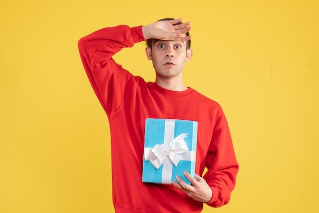 Vorderansicht junger mann mit rotem pullover, der hand auf seine stirn auf gelbem hintergrund setzt