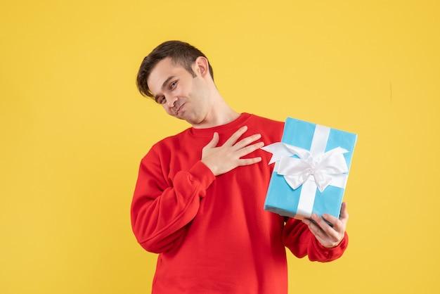 Vorderansicht junger mann mit rotem pullover, der hand auf seiner brust auf gelbem hintergrund setzt