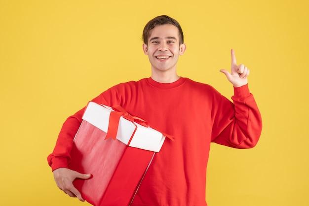 Vorderansicht junger mann mit rotem pulloverfinger, der auf gelbem hintergrund zeigt