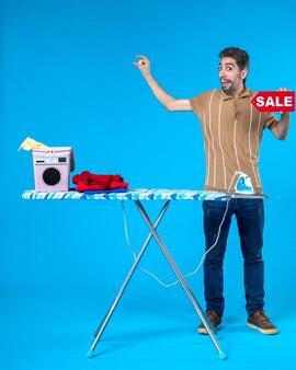Vorderansicht junger mann mit rotem verkauf schreiben auf blauem hintergrund hausarbeit wäsche sauber einkaufen hausfrau waschmaschine bügeleisen