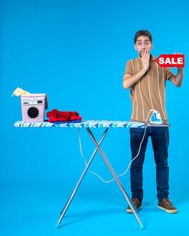 Vorderansicht junger mann mit rotem verkauf schreiben auf blauem hintergrund saubere hausfrau waschmaschine wäsche hausarbeit bügeleisen