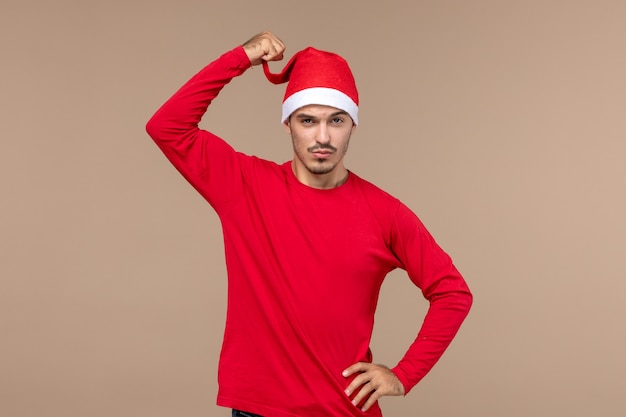 Vorderansicht junger mann mit rotem weihnachtsumhang auf braunem raum