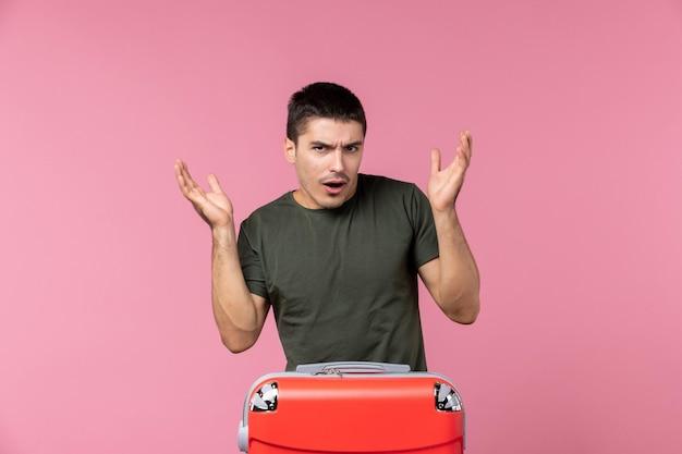 Vorderansicht junger mann mit roter tasche auf dem rosa raum