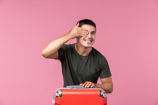 Vorderansicht junger mann mit roter tasche auf hellrosa raum