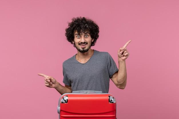 Vorderansicht junger mann mit roter tasche, die auf rosafarbenen raum zeigt