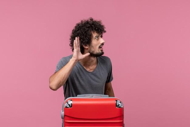 Vorderansicht junger mann mit roter tasche, die sich auf die reise vorbereitet, die auf rosafarbenem raum hört