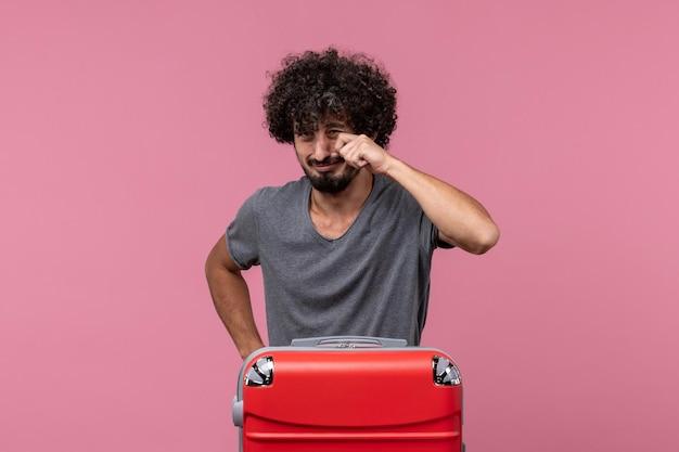Vorderansicht junger mann mit roter tasche, die sich auf die reise vorbereitet, die auf rosafarbenem raum weint