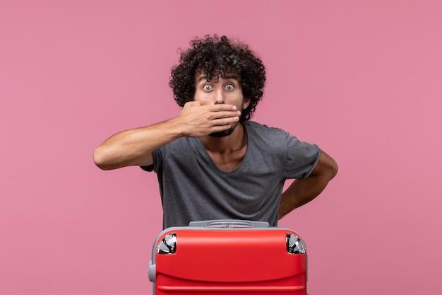 Vorderansicht junger mann mit roter tasche, die sich auf eine reise auf hellrosa raum vorbereitet