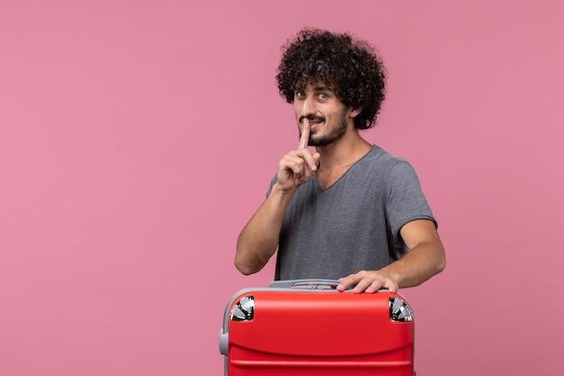 Vorderansicht junger mann mit roter tasche, die sich auf eine reise auf rosafarbenem raum vorbereitet