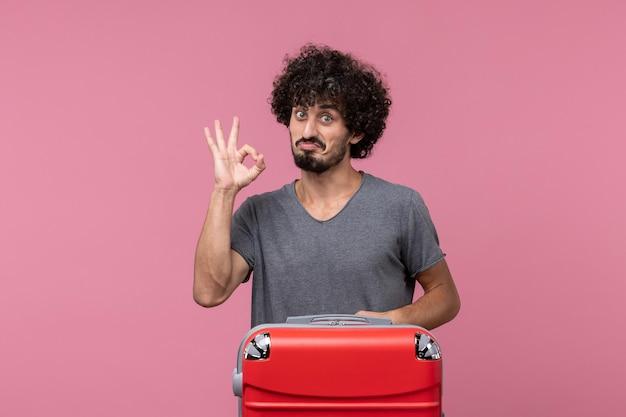 Vorderansicht junger mann mit roter tasche posiert auf dem rosa raum
