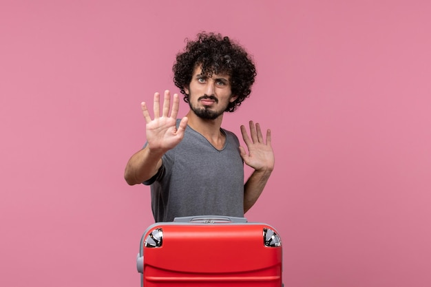 Vorderansicht junger mann mit roter tasche posiert auf hellrosa raum