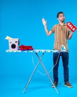 Vorderansicht junger mann mit roter verkaufsschrift auf blauem hintergrund hausarbeit wäsche einkaufen hausfrau waschmaschine bügeleisen sauber