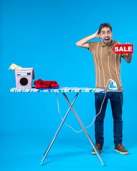 Vorderansicht junger mann mit roter verkaufsschrift auf blauem hintergrund sauber einkaufen hausfrau waschmaschine wäsche hausarbeit bügeleisen