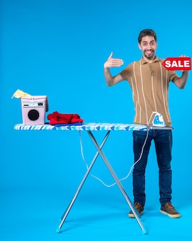 Vorderansicht junger mann mit roter verkaufsschrift auf blauem hintergrund sauber einkaufen hausfrau waschmaschine wäschebügel