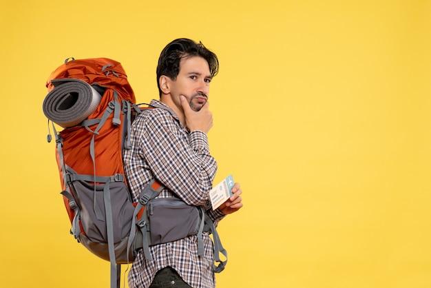 Vorderansicht junger mann mit rucksack, der ticket auf gelb hält
