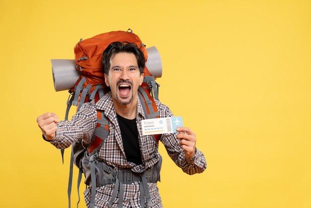 Vorderansicht junger mann mit rucksack, der ticket schreit, das auf gelb schreit