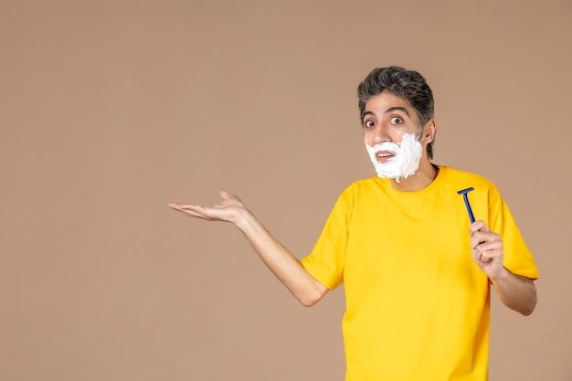 Vorderansicht junger mann mit schaum auf seinem gesicht, der rasiermesser auf rosa hintergrund hält