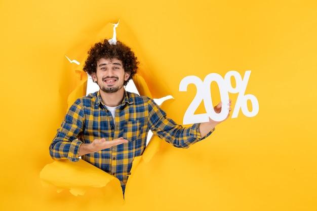 Vorderansicht junger mann mit schreiben lächelnd auf gelbem hintergrund