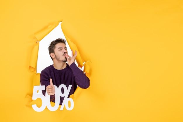Vorderansicht junger mann mit schrift auf gelbem hintergrund foto urlaub shopping geschenk verkauf farben weihnachten