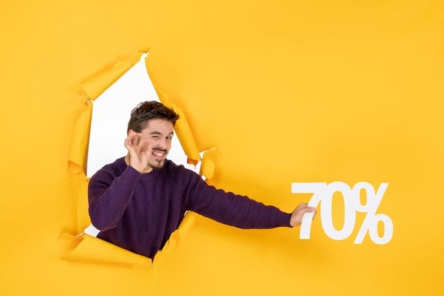 Vorderansicht junger mann mit schrift auf gelbem hintergrund weihnachtsfarbe urlaub shopping geschenk verkauf