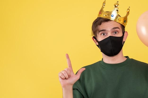 Vorderansicht junger mann mit schwarzer maske, die auf decke auf gelb zeigt