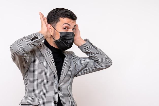 Vorderansicht junger mann mit schwarzer maske, die auf weißem lokalisiertem hintergrund steht