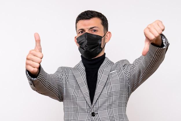 Vorderansicht junger mann mit schwarzer maske, die daumen oben und unten zeichen macht, das auf weißem lokalisiertem hintergrund steht