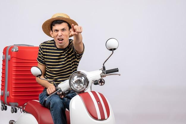Vorderansicht junger mann mit strohhut auf moped zeigt auf kamera