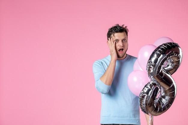 Vorderansicht junger mann mit süßen luftballons als marsch auf rosa hintergrund weiblicher frauentag sinnliche liebe ehe gleichheit datum spaß
